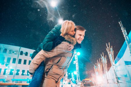 Photo for Cheerful and playful couple in warm winter outfits are fooling around evening city in the background - Royalty Free Image