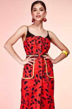 Photo pour Cheveux brune belle sexy jeune femme élégante avec le maquillage de soirée vêtu de soie rouge longue robe de vêtements de mode sac d'accessoires chaussures talons hauts de forme de corps parfait date party summer collection. - image libre de droit