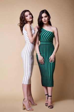 Photo for Two pretty beautiful sexy elegance woman skin tan body fashion model glamor pose wear trend dress casual clothes party summer collection makeup hair style brunette success accessory jewelry studio. - Royalty Free Image