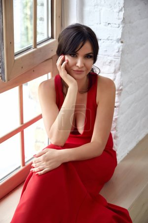 Photo pour Portrait brunette femme soirée maquillage siège sur la table mode style robe porter rouge couleur naturel salon de beauté cosmétique pour visage soins de la peau ongle main fond doré parfum . - image libre de droit