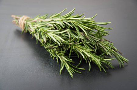 Photo for Sprigs of rosemary tied with string on a dark black background. - Royalty Free Image