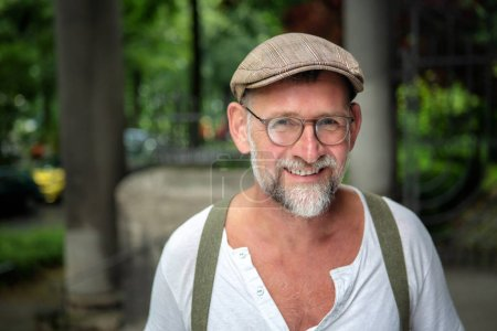 Photo for Portrait of handsome smiling bearded man with hat and eyeglasses in his 50s - Royalty Free Image