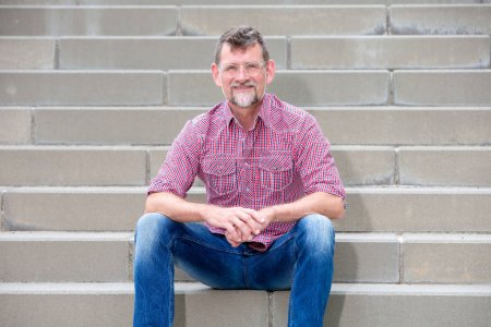 Photo for Portrait of handsome man in his 50s sitting on steps and smiling - Royalty Free Image