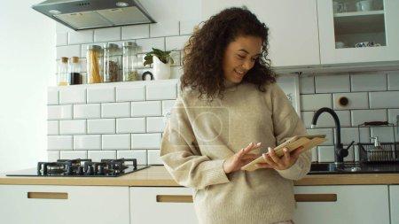 hübsche junge Frau mit digitalem Tablet in der gemütlichen Küche.