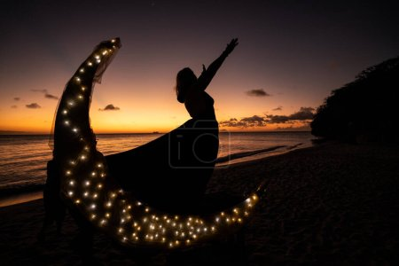 Photo for Silhouette of a woman in a black dress with a surfboard on the beach - Royalty Free Image