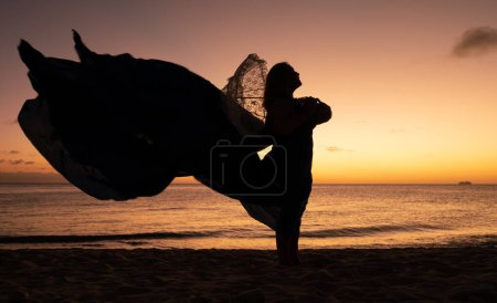 Photo for Silhouette of a man in a hat on the beach at sunset - Royalty Free Image