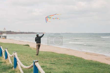 Photo pour Jeune homme court sur une plage paisible tout en élevant un cerf-volant coloré vers le ciel. Profiter d'une journée venteuse au bord de l'océan. Paysage balnéaire avec quelqu'un qui joue sur le rivage. Libre comme un oiseau concept, esprit zen - image libre de droit