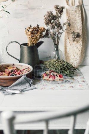 Photo pour Dessert Clafoutis à la cerise fraîchement cuite prêt à être servi avec de la vaisselle vintage. Tarte aux fruits de saison aux cerises de l'agriculture locale et biologique. Tarte française traditionnelle au décor rustique et campagnard. Cuisine Baker intérieur. - image libre de droit