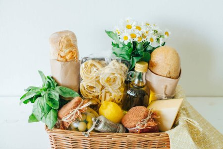 Italian food basket with ciabatta bread, tagliatelle, basil, olive oil, tomato sauce and marinated olives in a mason jar, lemon, cheese, pepper mill, napkin, and a bouqet of chamomiles.