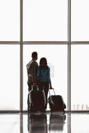 Back view.Young couple with suitcases