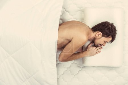 Top view.Young white bearded man sleeping in bed