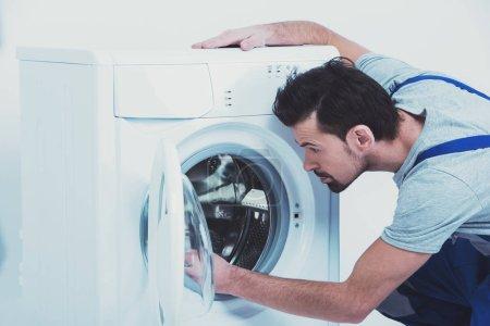 Side view of repairman checking washing machine.