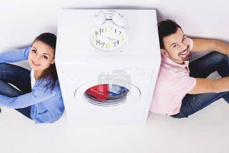 Photo pour Jeune couple en levant près de lave-linge. Radio-réveil sur machine à laver. Vue de dessus. - image libre de droit