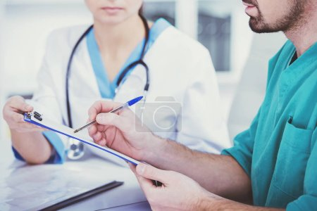 Doctor with assistant takes notes.