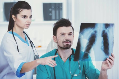 Doctor in green medical gown holds roentgen.