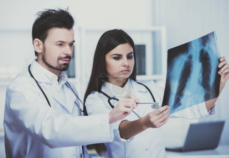 Medical staff looks at roentgen.