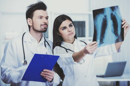 Two young doctors are looking at roentgen in clinic.