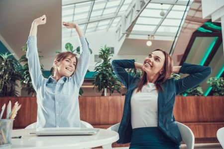 Two women exercising stretching in office.