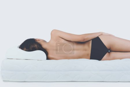 Young Bare Woman Lying on Orthopedic Mattress