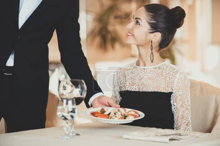 Waiter Serving Plate of Salad to Woman Guest