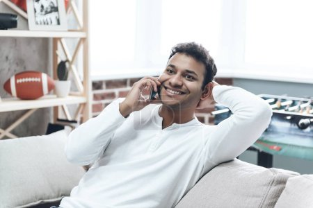 Smiling Guy in Casual Clothing using Cell Phone