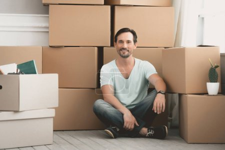 Bearded Caucasian Sits near Large Cardboard Boxes.