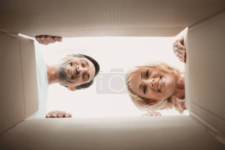 Photo for View from Bottom of Carton of Two Faces of an Adult Happy Married Couple. Caucasian Family. Blonde Woman. Moving House Concept. Young Man in Room. New Apartment Concepts. Unpacking Boxes. - Royalty Free Image
