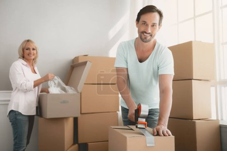 Photo for Packing Boxes with Building Tape in Order to Move to New Housing. Moving the Family to New Place. Family Gathers Things in Cardboard Boxes. Young Family in Room. New Apartment Concepts. - Royalty Free Image