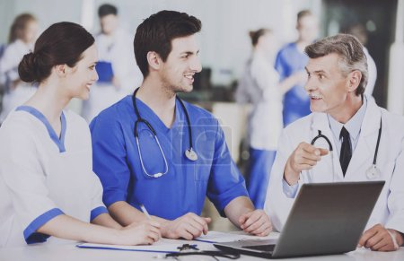 Group of Doctors with Laptop Discusses Operation.