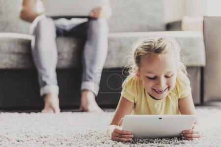 Photo pour Petite fille mignonne utilisant tablette numérique et souriant tout en s'allongeant sur le sol. Sur fond père utilisant ordinateur portable et assis sur canapé. Surfer sur le Web. Joyeux Famille. Détente à la maison. Fille avec dispositif numérique . - image libre de droit