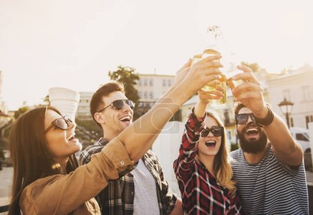 Photo for Young Happy People Have Fun Outdoors in Autumn. Drinking Beverages. Bottle of Beer. Fiendship Concept. Smiling People. Happy Friends. Communication with Friends Concept. Weekend in Autumn. - Royalty Free Image