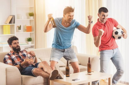 Young Men with Beer Watching Football at Home.