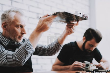 Two Men Repairing Hardware Equipment from PC. Repair Shop. Worker with Tools. Computer Hardware. Young and Old Workers. Modern Devices. Digital Device. Laptop on Desk. Electronic Devices Concept.