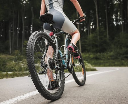 Young Woman Riding on Mountain Bicycle near Forest