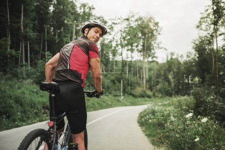 Young Man on Mountain Bicycle on Forest Road.