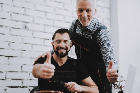 Photo for Two Exited Smiling Men in Uniform in Workshop. Repair Shop. Thumbs Up. Computer Hardware. Young and Old Workers. Modern Devices. Digital Device. Work in Workshop. Electronic Devices Concept. - Royalty Free Image