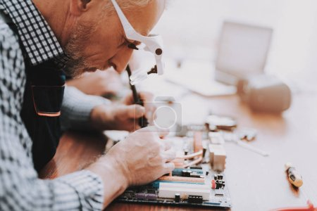 Photo for Close up. Old Man Repairing Motherboard from PC. Repair Shop. Worker with Tools. Computer Hardware. Magnifying Glass. Soldering Iron. Digital Device. Laptop on Desk. Electronic Devices Concept. - Royalty Free Image