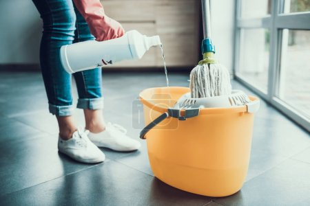 Woman in Gloves prepearing to Wipe Floor with Mop