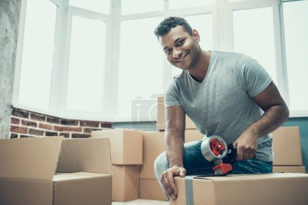 Photo for Young Smiling Man Packing Cardboard Box at Home. Happy Handsome Guy Preparing to Relocation by Packing Carton Boxes with Scotch Tape. Young Guy Moving to new Apartment - Royalty Free Image