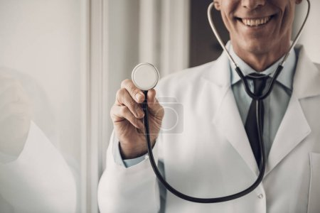 Photo for Happy Doctor hold Stethoscope. Healthcare Concept. Caucasian Adult Medicine Worker Standing in Hospital Wearing White Lab Coat Posing with Cheerful Expression. Pediatrician Occupation - Royalty Free Image