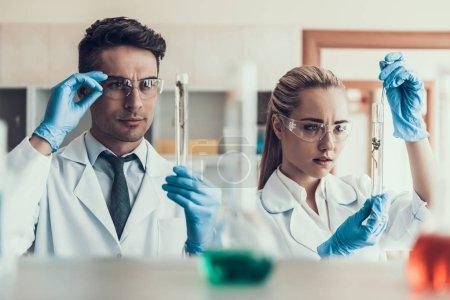 Photo pour Les jeunes scientifiques regardent Sampes en laboratoire. Des chercheurs portant des manteaux blancs, des gants et des lunettes de protection examinant des échantillons liquides chimiques dans des flacons. Scientifiques au travail en laboratoire - image libre de droit