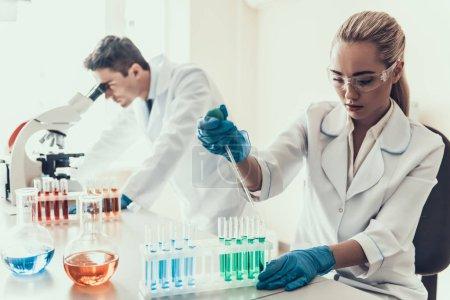 Photo pour Jeunes scientifiques examinant des échantillons en laboratoire. Chercheuse femelle regardant des échantillons chimiques liquides dans des Flacons tandis que le scientifique masculin utilisant le microscope. Scientifiques à l'œuvre en laboratoire - image libre de droit