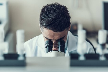 Photo for Young Scientist using Microscope in Laboratory. Male Researcher wearing white Coat sitting at Desk and looking at Samples by using Microscope in Lab. Scientist at Work in Laboratory - Royalty Free Image