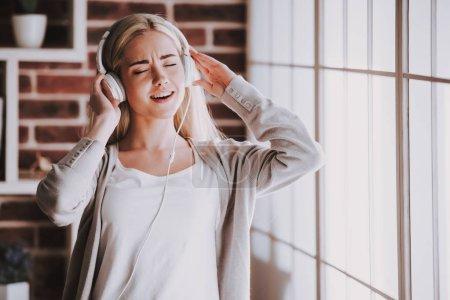 Photo pour Jeune femme de sourire écoutant la musique dans des écouteurs. Belle femme blonde dans la tenue occasionnelle et les yeux fermés restant à côté de la fenêtre et de la musique d'écoute d'enjoing dans des écouteurs à la maison. - image libre de droit