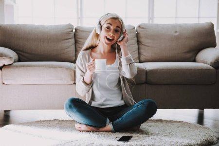 Photo pour Jeune femme de sourire écoutant la musique dans des écouteurs. Belle fille s'asseyant sur le tapis à côté de tasse de sofa retenant du café et appréciant la musique d'écoute dans des écouteurs reliés au smartphone - image libre de droit