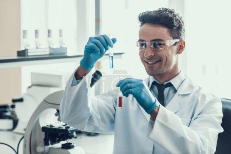 Photo pour Le scientifique examine les échantillons liquides dans des fioles en laboratoire. Jeune chercheur souriant portant des gants de manteau blanc et des lunettes de protection examinant des échantillons liquides chimiques. Scientifique au travail en laboratoire - image libre de droit
