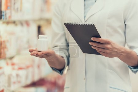 Closeup Pharmacist holds Pills Bottle and Notebook