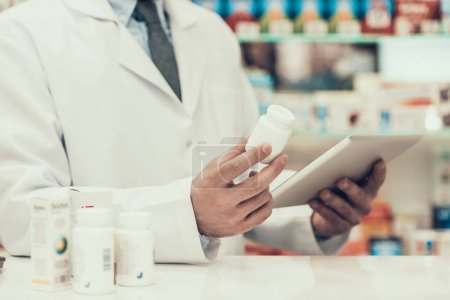 Closeup Pharmacist Holding Pills Bottle and Tablet