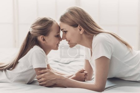Photo for Young Happy Mother and Little Doughter Together. Beautiful Smiling Woman spending time with Cute Adorable Daughter. Mom and Child lying on Bed at Home. Family and Motherhood Concept - Royalty Free Image