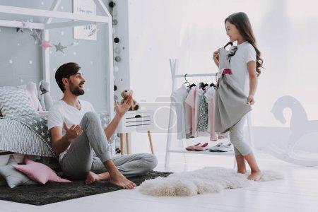 Ojciec pomagając dziewczyna wybierając sukienkę w sypialni. Pretty Little Happy Girl Sneaking wśród ubrań w szafie. Ubierz ubrania wiszące na bieliźnie dla wyobraźni lub koncepcji kreatywności.